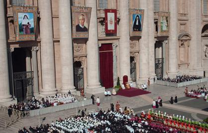 Pope Benedict XVI sits below four images of newly canonized Saints