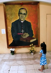 PARISHIONER TOUCHES IMAGE OF ARCHBISHOP OSCAR ROMERO ON 29TH ANNIVERSARY OF HIS DEATH. CNS photo/Luis Galdamez, Reuters