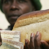 ZIMBABWEAN WOMAN HOLDS LOAF OF BREAD IN 2006