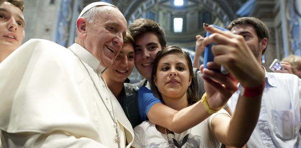 Pope Francis poses with youths during meeting with young people in St. Peter's Basilica at Vatican