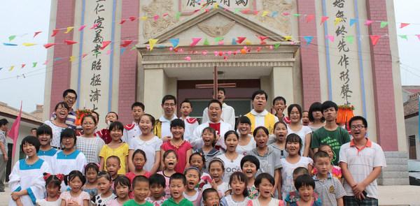 Children gather with priests during parish anniversary in village in western China
