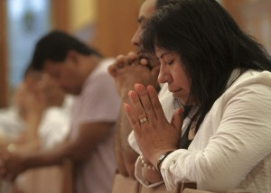 People pray during Spanish-language Mass in Riverhead, N.Y.