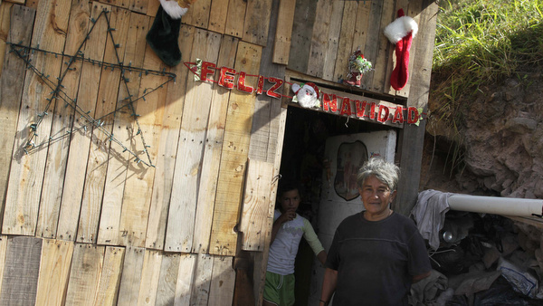 Woman and girl stand outside home in poor neighborhood of Honduras