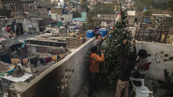 Pakistani boys decorate Christmas tree on roof of house in Islamabad