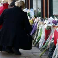 Well-wishers comfort each other as they place bouquet near site of police helicopter crash in Scotland