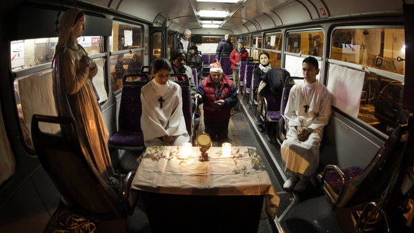 PEOPLE PRAY IN BUS DURING CHRISTMAS MASS FOR HOMELESS IN FRANCE