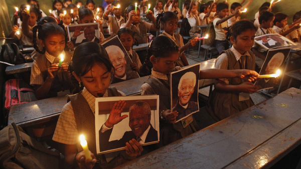 Schoolchildren hold candles and portraits of former South African President Mandela during prayer ceremony in India