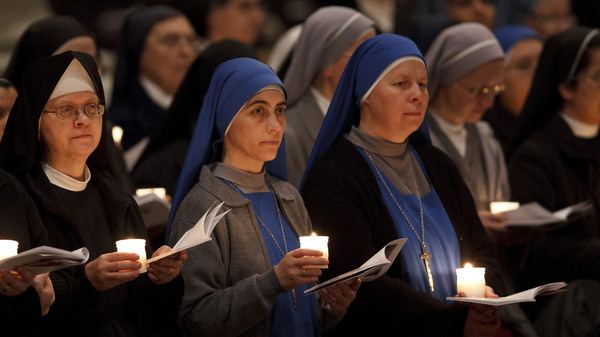 Nuns hold candles as pope celebrates Mass at Vatican