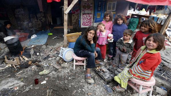 Syrian refugee children gather around a fire near their makeshift tents in central Ankara