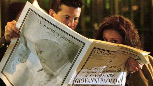 FILE PHOTO OF COUPLE READING VATICAN NEWSPAPER FOLLOWING DEATH OF POPE