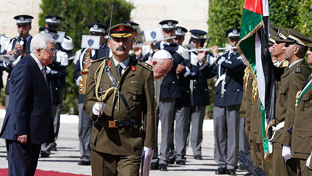 Pope Francis bows towards the flag of the Palestinian Authority as he reviews the honor guard during an arrival ceremony with Palestinian President Mahmoud Abbas, left, at the presidential palace in Bethlehem, West Bank, May 25. (CNS photo/Paul Haring)