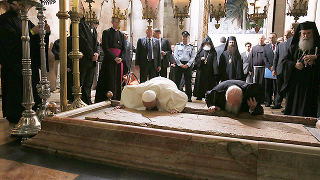 Pope Francis and Ecumenical Patriarch Bartholomew of Constantinople kiss the Stone of Unction in Jeusalem's Church of the Holy Sepulcher May 25. The two leaders marked the 50th anniversary of the meeting in Jerusalem between Pope Paul VI and Patriarch At henagoras. (CNS photo/Grzegorz Galazka, pool)