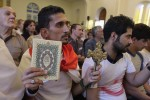 Iraqi man carrying cross and Quran attends Mass  in Baghdad
