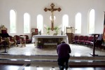 MAN KNEELS IN PRAYER IN TABERNACLE AT CHALDEAN, ASSYRIAN CHURCH IN CALIFORNIA