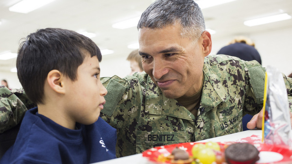 Navy Reserve Petty Officer Jesus Benitez talks with his son, Maddox, after surprising him and his sister, Mia, at St. Joan of Arc School in Aberdeen, Md., Dec. 18. His children did not know he was able to come home for the holidays. Benitez is in the middle of a yearlong deployment in Djibouti, on the Horn of Africa, where he expected to be celebrating Christmas this year. (CNS photo/Tom McCarthy Jr.) See BENITEZ Dec. 23, 2014.