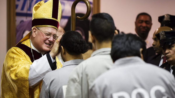 New York Cardinal Timothy M. Dolan blesses an inmate as he celebrates Christmas Eve Mass at Rikers Island correctional facility in New York Dec. 24. (CNS photo/Lucas Jackson, Reuters) (Dec. 26, 2013)
