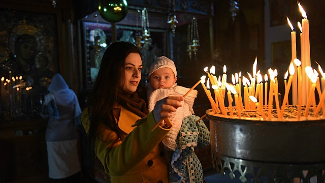 Palestinian Manan Abu Abuayash holds her baby Maram, 6 months, while lighting candles Dec. 20 in the Church of the Nativity where tradition believes Christ was born in Bethlehem, West Bank. Few tourists are visiting Bethlehem this Christmas season because of the recent violence between Israelis and Palestinians. (CNS photo/Debbie Hill)
