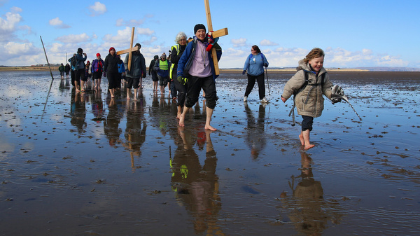 Pilgrims walk across tidal causeway while carrying crosses during pilgrimage in northern England