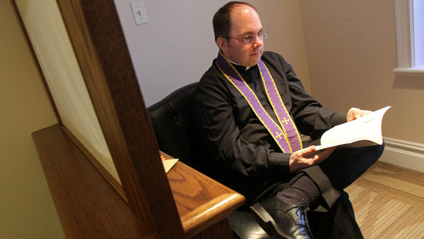Priest reads during brief break between hearing confessions at New York church