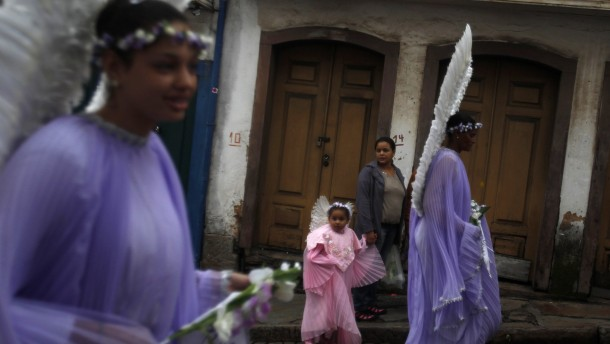 Child dressed as angel walks alongside women during Easter Sunday procession in Brazil