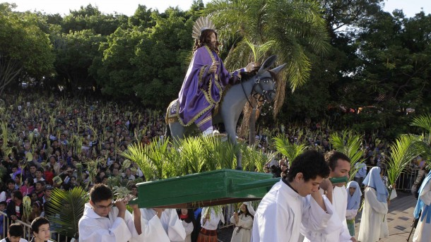 Pilgrims carry statue of Christ on donkey during Palm Sunday procession outside cathedral in Paraguay