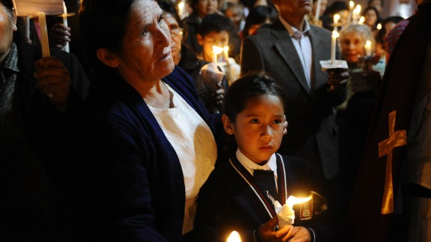 WOMAN AND GIRL TAKE PART IN PROCESSION DURING HOLY WEEK CELEBRATIONS IN PERU
