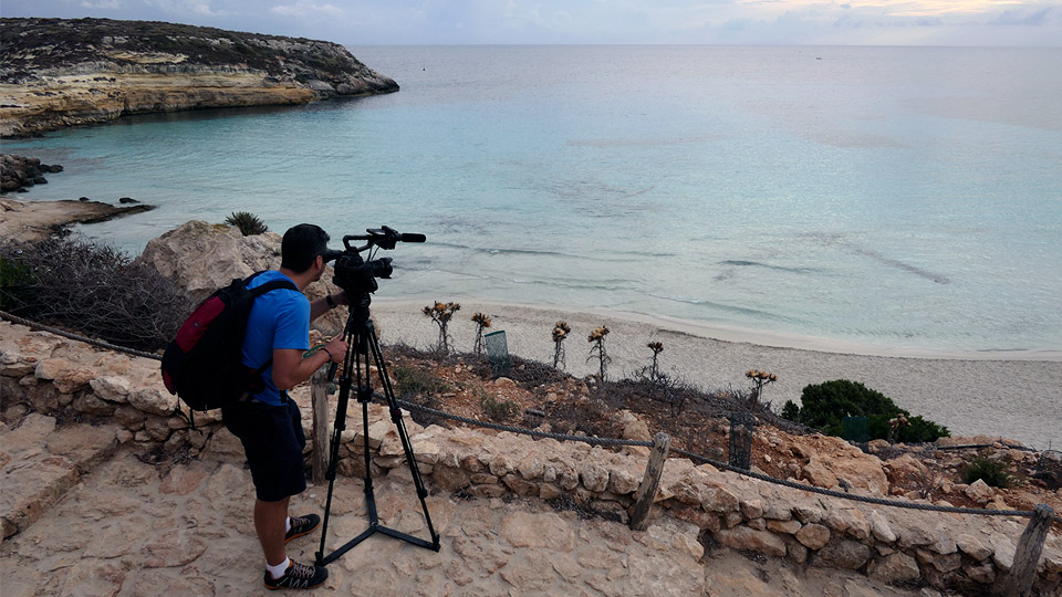 Peter Turek looks through the lens of a camera at a beach in Lampedusa and the blue Mediterranean