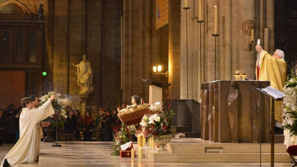 A priest elevates the host in Notre Dame Cathedral in Paris