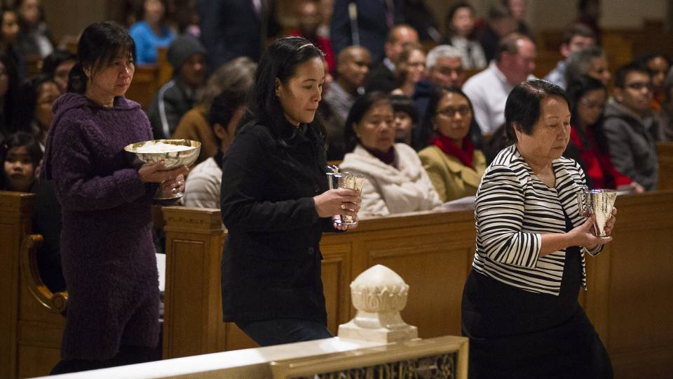 Women bring offertory gifts to the altar during Mass
