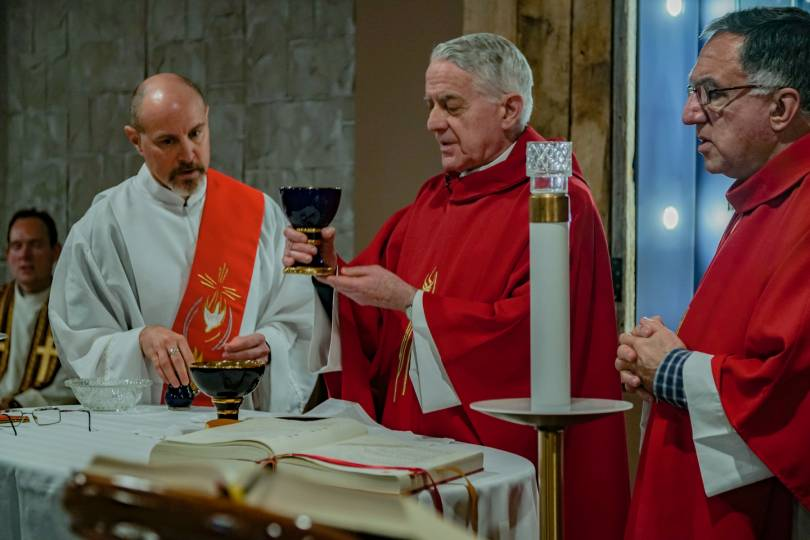 Two priests and a deacon during the preparation of the gifts at Mass