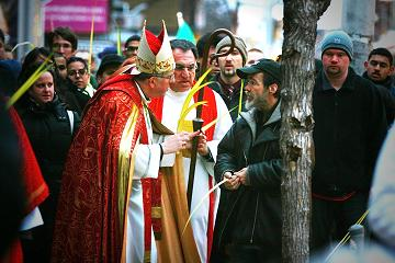 Archbishop Thomas Collins blesses a passerby along Toronto's Queen Street East