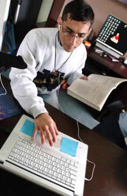 SEMINARIAN WORKS AT LAPTOP DURING PODCAST AT NEW YORK CHURCH