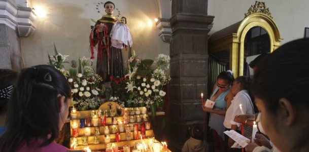 WOMEN PRAY AROUND STATUE OF ST. ANTHONY IN MEXICO