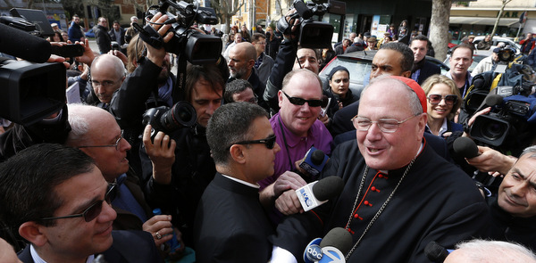Media surround U.S. Cardinal Dolan as he arrives to celebrate Mass at titular church in Rome