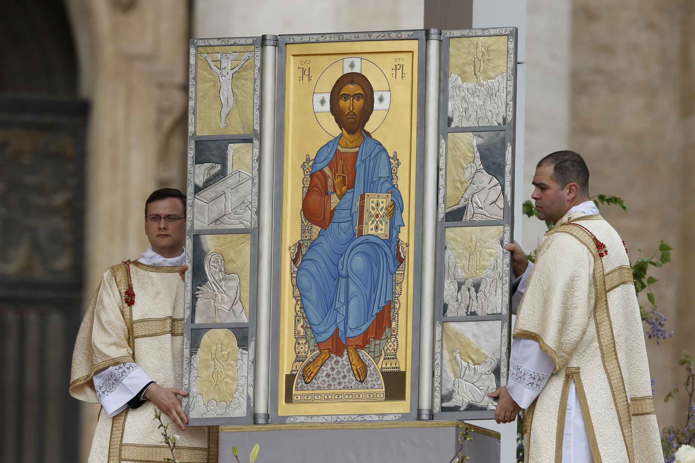 Altar servers unveil image of Jesus as pope celebrates Easter Mass in St. Peter's Square at Vatican
