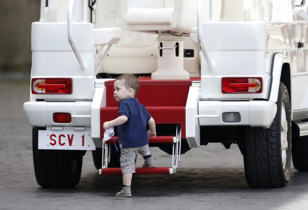 Boy climbs steps of popemobile during pope's weekly audience in St. Peter's Square at Vatican