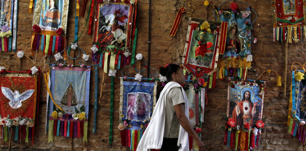 Woman walks past religious icons hanging on a wall during celebrations for the feast of  St. George in Rio de Janeiro
