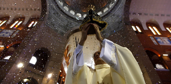 PRIEST HOLDS IMAGE OF MARY DURING MASS INSIDE BASILICA IN BRAZIL