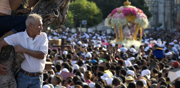 MAN WATCHES PILGRIMS CARRY IMAGE OF OUR LADY DURING PROCESSION IN BRAZIL