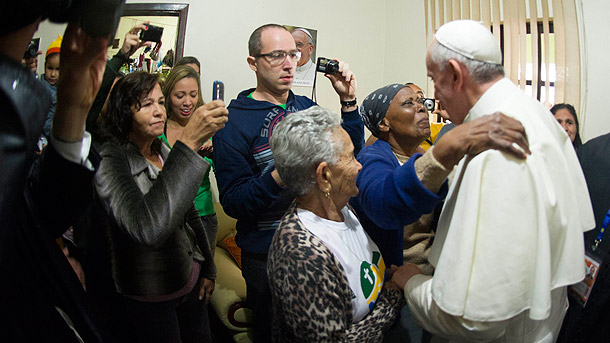 Pope Francis is embraced by a woman during a visit with residents at a home in the Varginha slum in Rio de Janeiro July 25. (CNS photo/L'Osservatore Romano via Reuters)