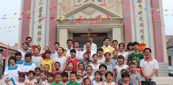 Children gather with priests during parish anniversary in village in western China