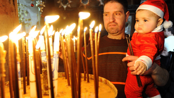 PALESTINIAN CATHOLIC LIGHTS CANDLE INSIDE CHURCH OF NATIVITY ON CHRISTMAS EVE
