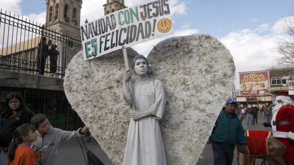 CHILDREN TOUCH WINGS OF MAN DRESSED AS ANGEL IN MEXICO