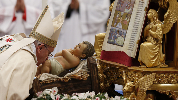 Pope Francis kisses figurine of baby Jesus as he leaves Mass on feast of Epiphany at Vatican
