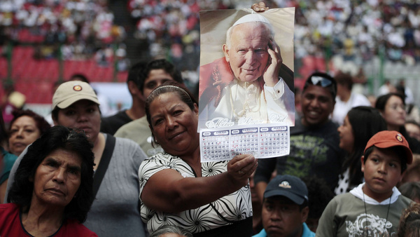 WOMAN HOLDS IMAGE OF POPE JOHN PAUL II DURING EVENT MARKING ANNIVERSARY OF HIS DEATH