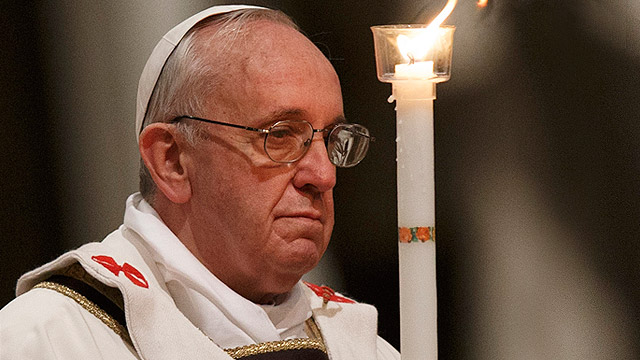 Pope Francis holds a candle as he celebrates the Easter Vigil