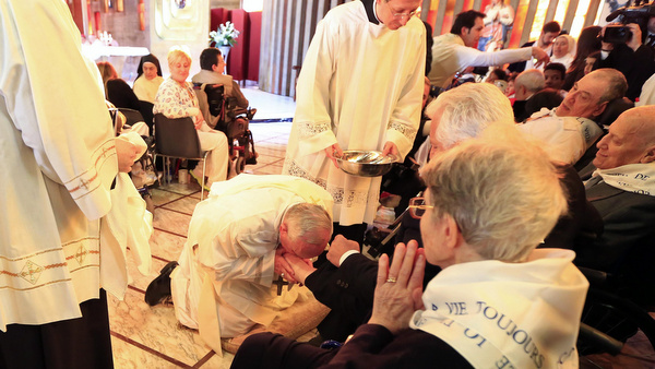 Pope Francis kisses a foot of a disabled person Our Lady of Providence Center in Rome