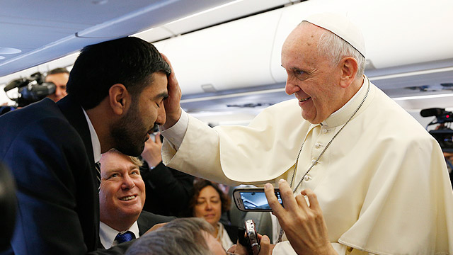 Pope Francis blesses a Palestinian journalist aboard the papal plane on his flight to Amman, Jordan, May 24, the start of his three-day visit to the Holy Land. (CNS photo/Paul Haring)