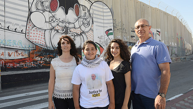 Family chosen to eat with pope after Mass in Bethlehem George Sbait and his wife, Shadia, pose with their children, Caesar, 13, and Nicole, 15, in front of a section of the Israeli separation wall in Bethlehem, West Bank, May 24. The Sbaits had lunch with Pope Francis in Bethlehem May 25. (CNS photo/Debbie H ill)