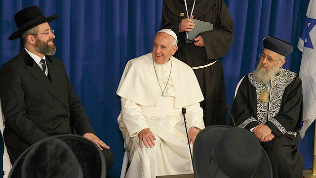 """Pope Francis visits with Israel's two chief rabbis, Ashkenazi Rabbi David Lau, left, and Sephardic Rabbi Yitzhak Yosef, in at the Heichal Shlomo center in Jerusalem May 26. Looking on is the pope's translator. The pope told them that Jews were not collec tively responsible for the death of Jesus and called on Christians and Jews to develop greater appreciation for their common """"spiritual heritage,"""" through deeper knowledge of each other's faith, especially among the young. (CNS photo/Paul Haring)"""